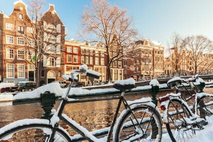 Kanal in Amsterdam im Winter mit zugeschneiten Fahrrädern