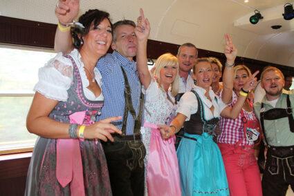 Feiernde Gruppe im Tanzwagen des Partyzugs auf dem Weg nach Cannstatt