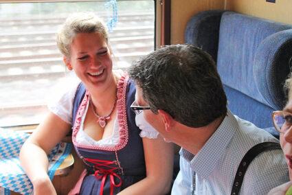 Mann und Frau unterhalten sich im Sitzabteil des Partyzuges auf dem Weg nach Cannstatt
