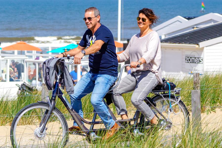 Ein Pärchen fährt mit einem Tandem durch Egmond aan Zee