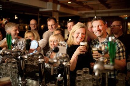 Pärchen trinkt gemeinsam Bier an der Theke in der Brasserie in Egmond aan Zee