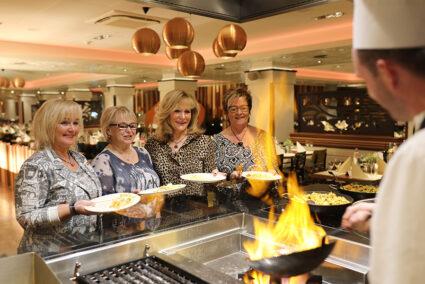 Vier Frauen stehen am LIve-Cooking-Buffet in Egmond aan Zee