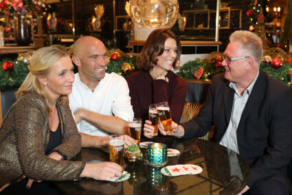 Gruppe sitzt an einem Tisch und trinkt Bier in der weihnachtlich geschmückten Brasserie in Egmond aan Zee