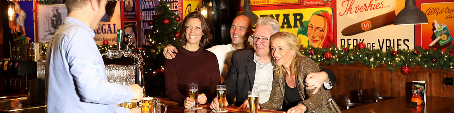 Gruppe an der Bar im weihnachtlich geschmückten Pub in Egmond aan Zee