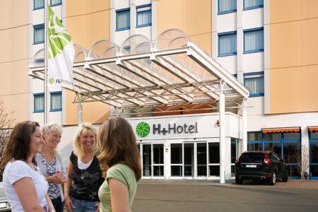Frauengruppe vor dem Eingangsbereich des H+ Hotel Leipzig-Halle in Halle
