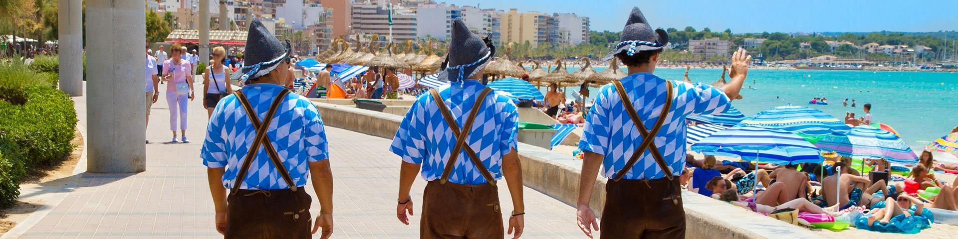 Drei Männer im Bayern-Outfit an der Strandpromenade auf Mallorca