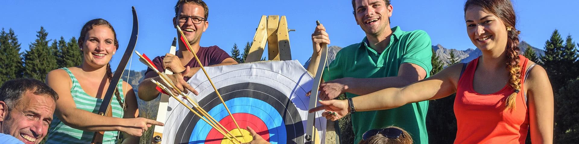 Gruppe steht an einer Zielscheibe vom Bogenschießen in Neuharlingersiel