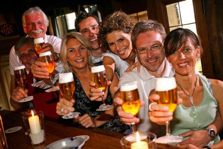 Gruppe trinkt gemeinsam Bier im U-Fleku